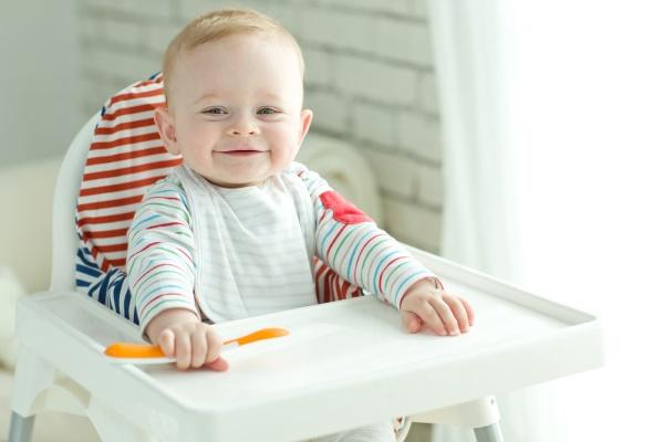 Младенец в стульчике для кормления