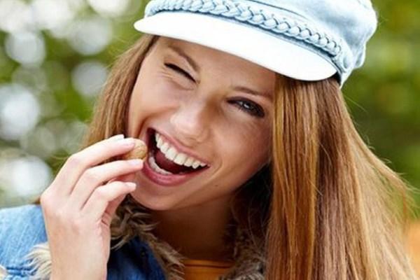 Девушка ест орехи