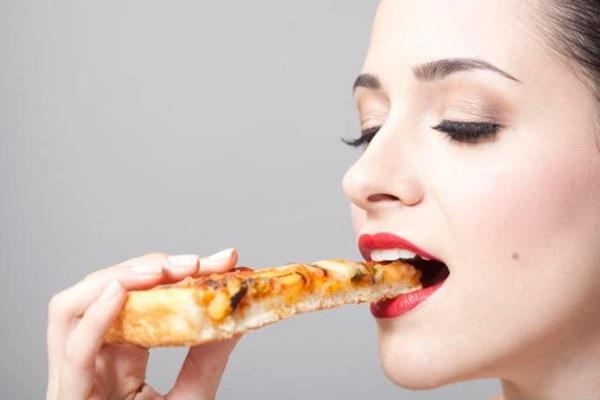 Девушка ест пиццу