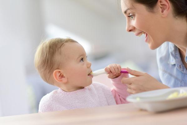 Мать кормит ребенка кашей с ложки