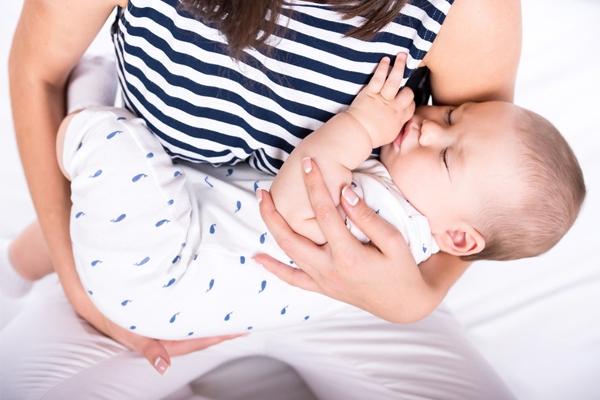 Младенец спит на руках у мамы