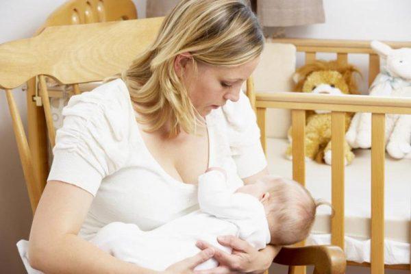 Женщина кормит младенца грудью