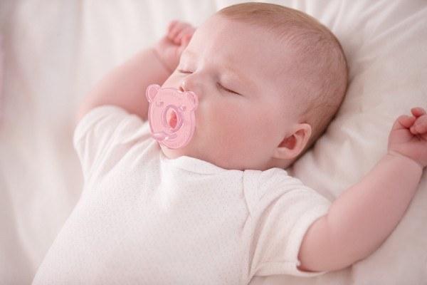 Младенец спит с соской во рту