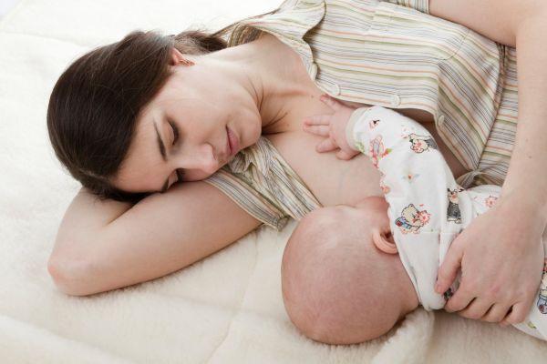 Девушка кормит ребенка грудью лежа