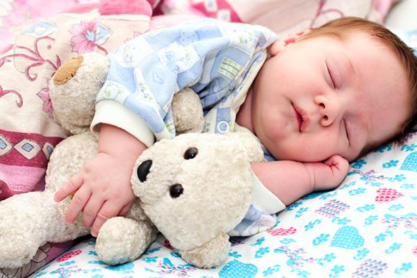 Грудничок спит с игрушкой в руках