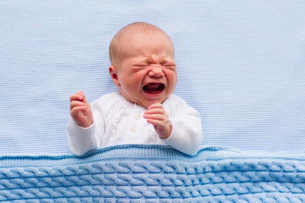 Плачущий младенец в кровати