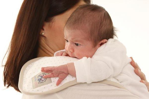 Мать держит новорожденного на плече