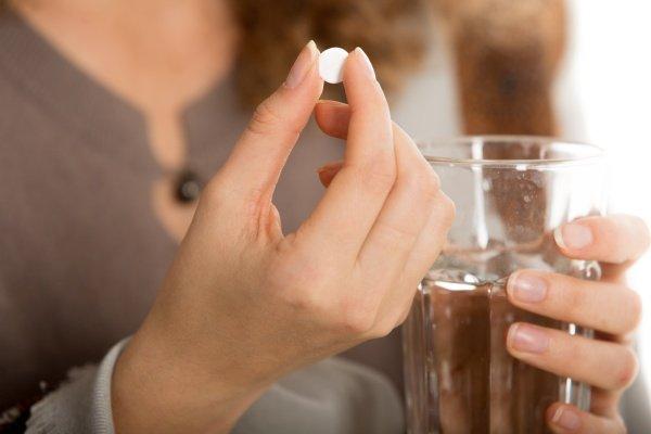 Женщина держит таблетку в руке