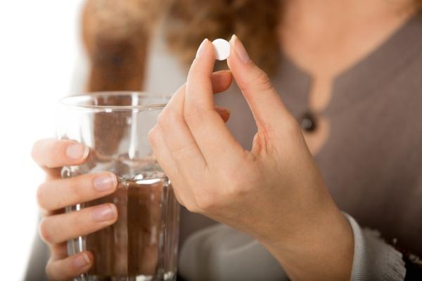 Девушка принимает таблетку