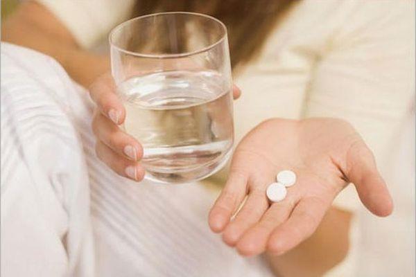 Таблетки в руке и стакан воды