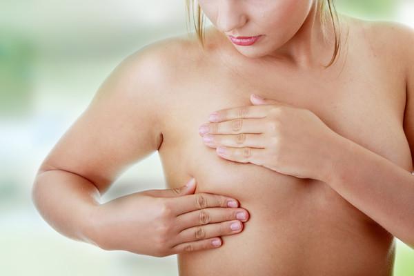 Девушка ощупывает свою грудь