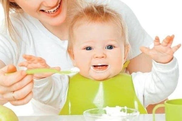 Ребенок кушает прикорм из ложки