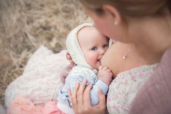 Девушка кормит ребенка грудью на улице
